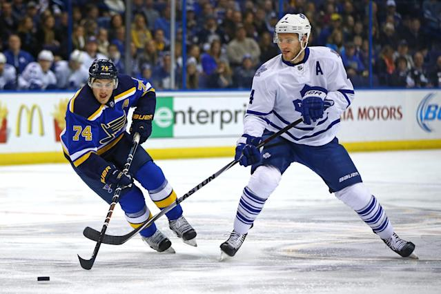 St. Louis Blues' T.J. Oshie and Toronto Maple Leafs' Cody Franson go after the puck during the first period of an NHL hockey game Saturday, Jan. 17, 2015, in St. Louis. (AP Photo/Billy Hurst)
