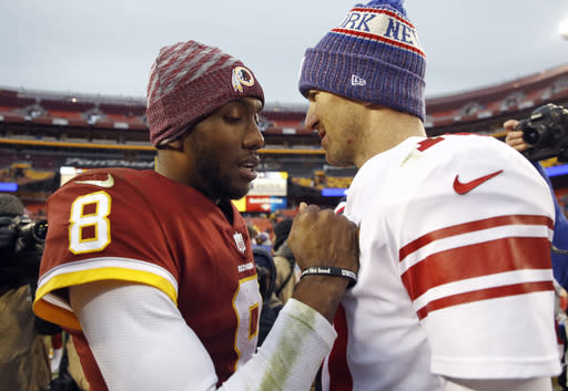 Washington Redskins quarterback Josh Johnson (8) talks with New York Giants quarterback Eli Manning, right, after an NFL football game Sunday, Dec. 9, 2018, in Landover, Md. (AP Photo/Patrick Semansky)