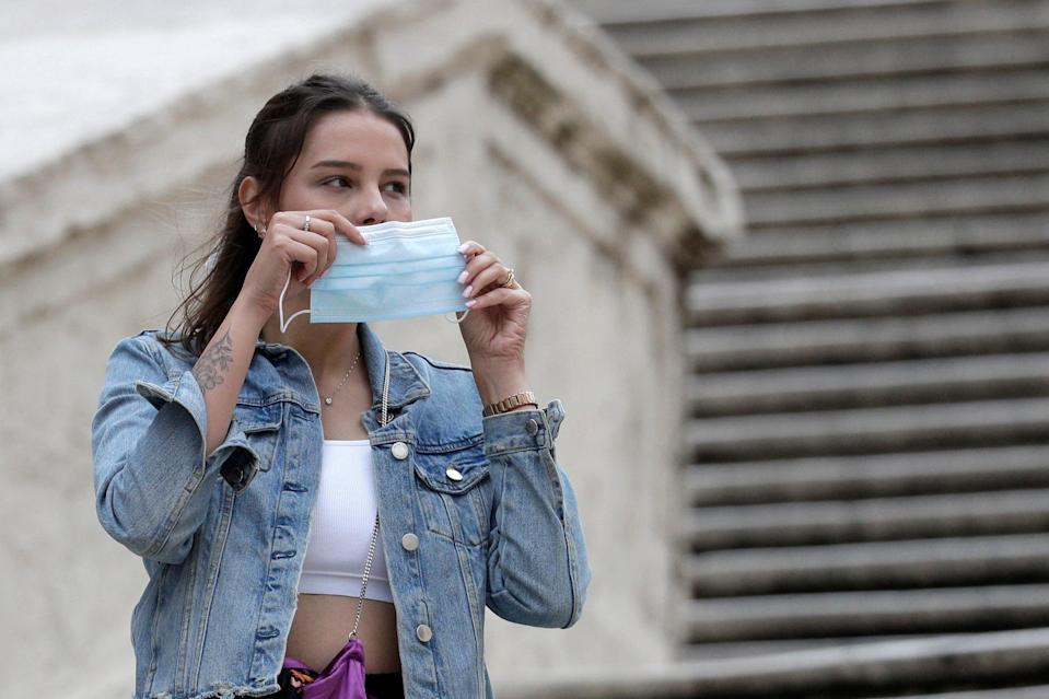 A woman puts on a face mask in Rome on 6 October, 2020.  (AP)