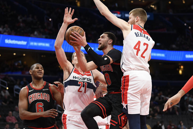 Chicago Bulls guard Zach LaVine (8) goes to the basket next to Washington Wizards forward Moritz Wagner (21) and forward Davis Bertans (42) during the first half of an NBA basketball game, Tuesday, Feb. 11, 2020, in Washington. (AP Photo/Nick Wass)