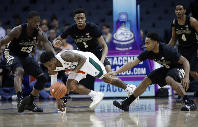 Miami's Chris Lykes, center, recovers a loose ball as Wake Forest players Chaundee Brown (23), Isaiah Mucius (1) and Brandon Childress (0) defend during the first half of an NCAA college basketball game in the Atlantic Coast Conference tournament in Charlotte, N.C., Tuesday, March 12, 2019. (AP Photo/Nell Redmond)