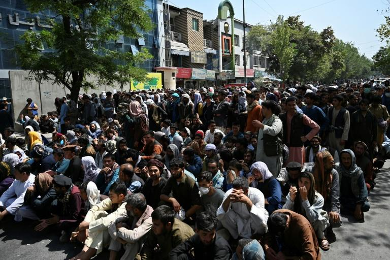 People sit along a road outside a bank in Kabul waiting to withdraw money on September 4, 2021 (AFP/WAKIL KOHSAR)