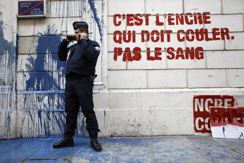 """A riot police officer stand by a protest sign """"It's ink, not blood that should run"""" stenciled on the wall of Syrian embassy in Paris by Members of French watchdog organization Reporters Without Borders (RSF), Tuesday May 3, 2011. This action marks World Press Freedom Day. (AP Photo/Thibault Camus)"""