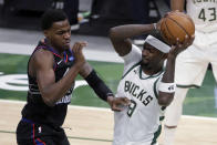 Milwaukee Bucks' Bobby Portis (9) controls a rebound next to Philadelphia 76ers' Paul Reed during the second half of an NBA basketball game Thursday, April 22, 2021, in Milwaukee. (AP Photo/Aaron Gash)