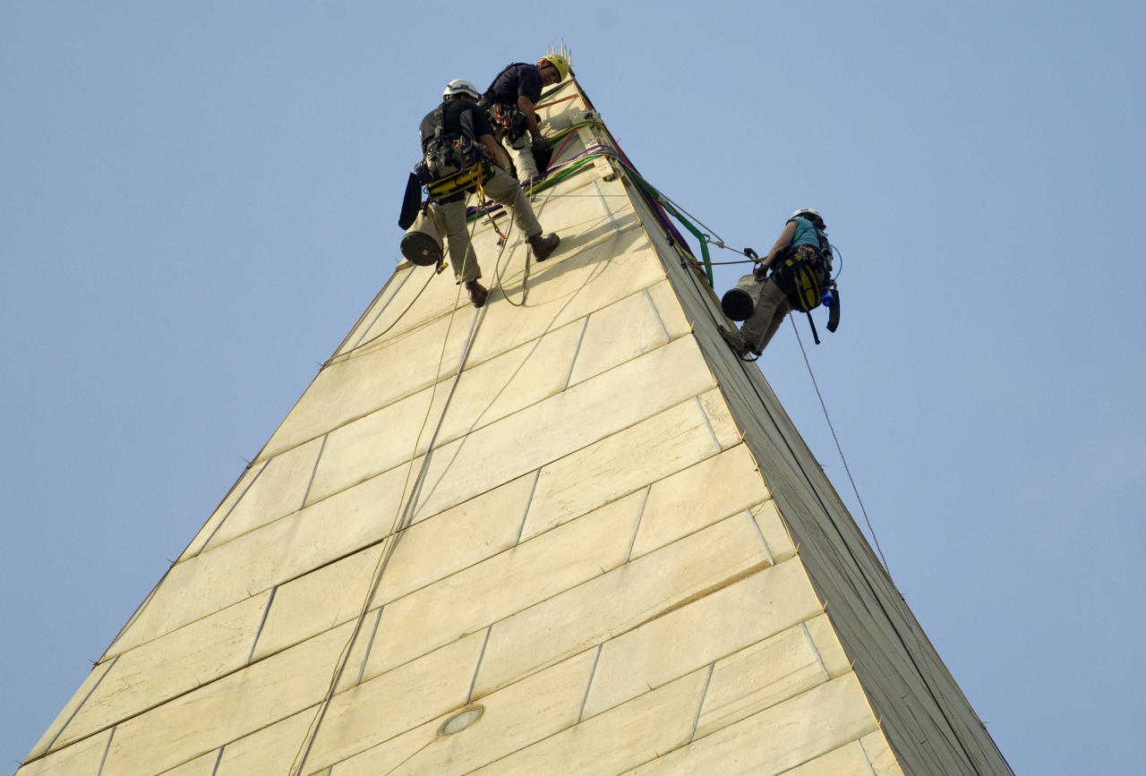 Dan Gach, left, Erik Shon, center, and Emma Cardini inspect the exterior of the Washington Monument for damage caused by last months earthquake on Wednesday, Sept. 28, 2011, in Washington. (AP Photo/Evan Vucci)