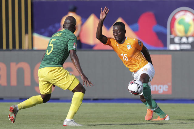 Ivory Coast's Max Gradel, right, goes for the ball past South Africa's Thamsanqa Mkhize during the African Cup of Nations group D soccer match between Ivory Coast and South Africa in Al Salam Stadium in Cairo, Egypt, Monday, June 24, 2019. (AP Photo/Hassan Ammar)