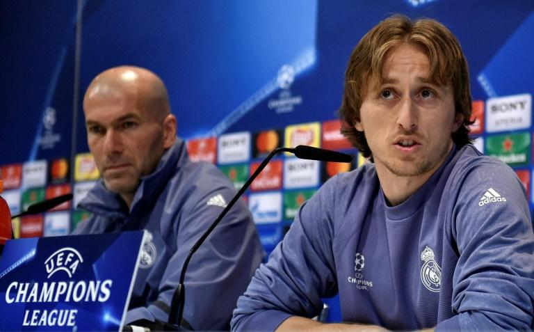 Real Madrid's midfielder Luka Modric speaks next to Real Madrid's coach Zinedine Zidane (L) during a press conference on February 14, 2017, on the eve of the UEFA Champions League football match Real Madrid vs Napoli