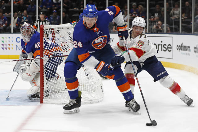 Florida Panthers center Frank Vatrano (77) tries to get the puck from New York Islanders defenseman Scott Mayfield (24) as Islanders goaltender Semyon Varlamov (40) watches during the first period of an NHL hockey game Saturday, Oct. 12, 2019, in Uniondale, N.Y. (AP Photo/Kathy Willens)