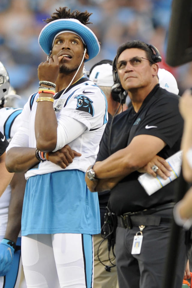 Carolina Panthers quarterback Cam Newton watches a replay with Carolina Panthers head coach Ron Rivera on the sidelines during the first half an NFL preseason football game against the Buffalo Bills, Friday, Aug. 16, 2019, in Charlotte, N.C. (AP Photo/Mike McCarn)