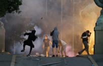 Protesters clash with Serbian riot police in Belgrade, Serbia, Wednesday, July 8, 2020. Police have fired tear gas at protesters in Serbia's capital during the second day of demonstrations against the president's handling of the country's coronavirus outbreak. President Aleksandar Vucic backtracked on his plans to reinstate a coronavirus lockdown in Belgrade this week, but it didn't stop people from firing flares and throwing stones while trying to storm the downtown parliament building. (AP Photo/Darko Vojinovic)