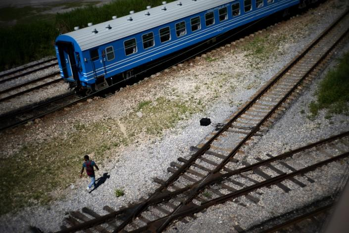 A man walks near the first train using new equipment from China rides past, in Havana, Cuba, Saturday, July 13, 2019. The first train using new equipment from China pulled out of Havana Saturday, hauling passengers on the start of a 915-kilometer (516-mile) journey to the eastern end of the island as the government tries to overhaul the country's aging and decrepit rail system. (AP Photo/Ramon Espinosa)