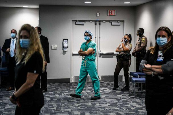 PHOTO: A doctor listens to the governor of Florida during a press conference to address the rise of coronavirus cases in the state, at Jackson Memorial Hospital in Miami, July 13, 2020. (Chandan Khanna/AFP via Getty Images)