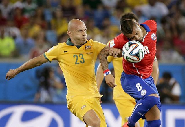 Australia's Mark Bresciano, left, and Chile's Arturo Vidal battle for the ball during the group B World Cup soccer match between Chile and Australia at the Arena Pantanal in Cuiaba, Brazil, Friday, June 13, 2014. (AP Photo/Felipe Dana)