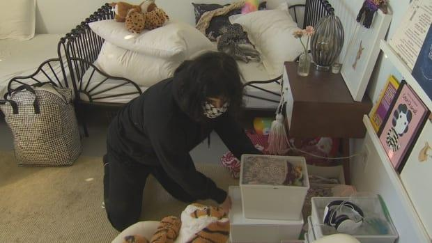 """Building resident and single mother of two Tahsin Davdani packs up her daughters' room. She says residents need more help to face this """"panicky"""" situation they're now in."""