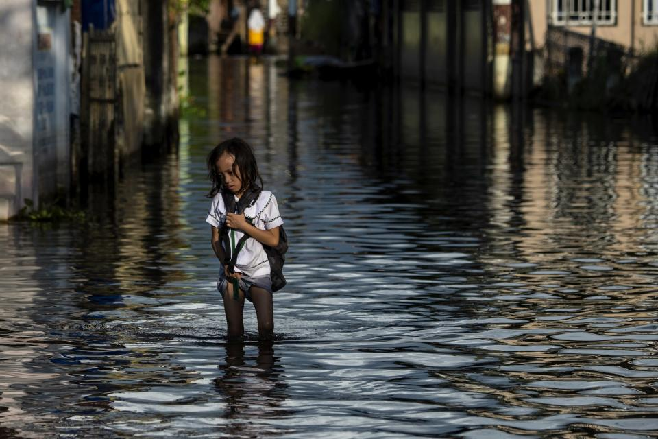 An elementary student wading through floodwaters in Mabalacat, Pampanga, Philippines