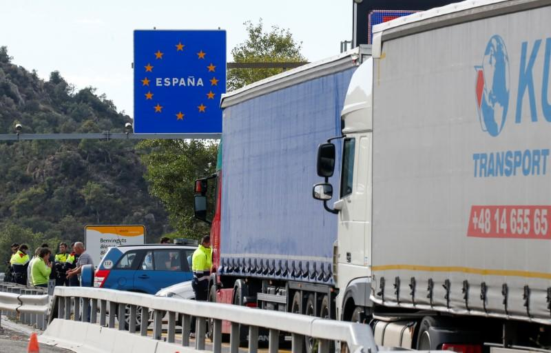 Spanish police officers and drivers stand on the motorway in Le Perthus near the Franco-Spanish border as Catalan demonstrators block the Spanish motorway during Catalonia's general strike