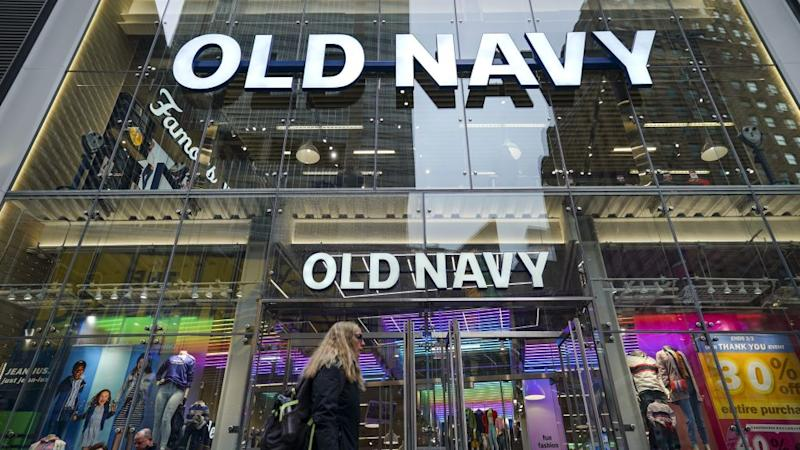 A pedestrian walks past a colorful Old Navy store in Times Square