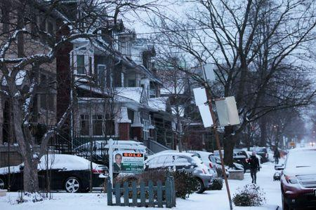 House sold sign is seen after an overnight snow storm, in Toronto