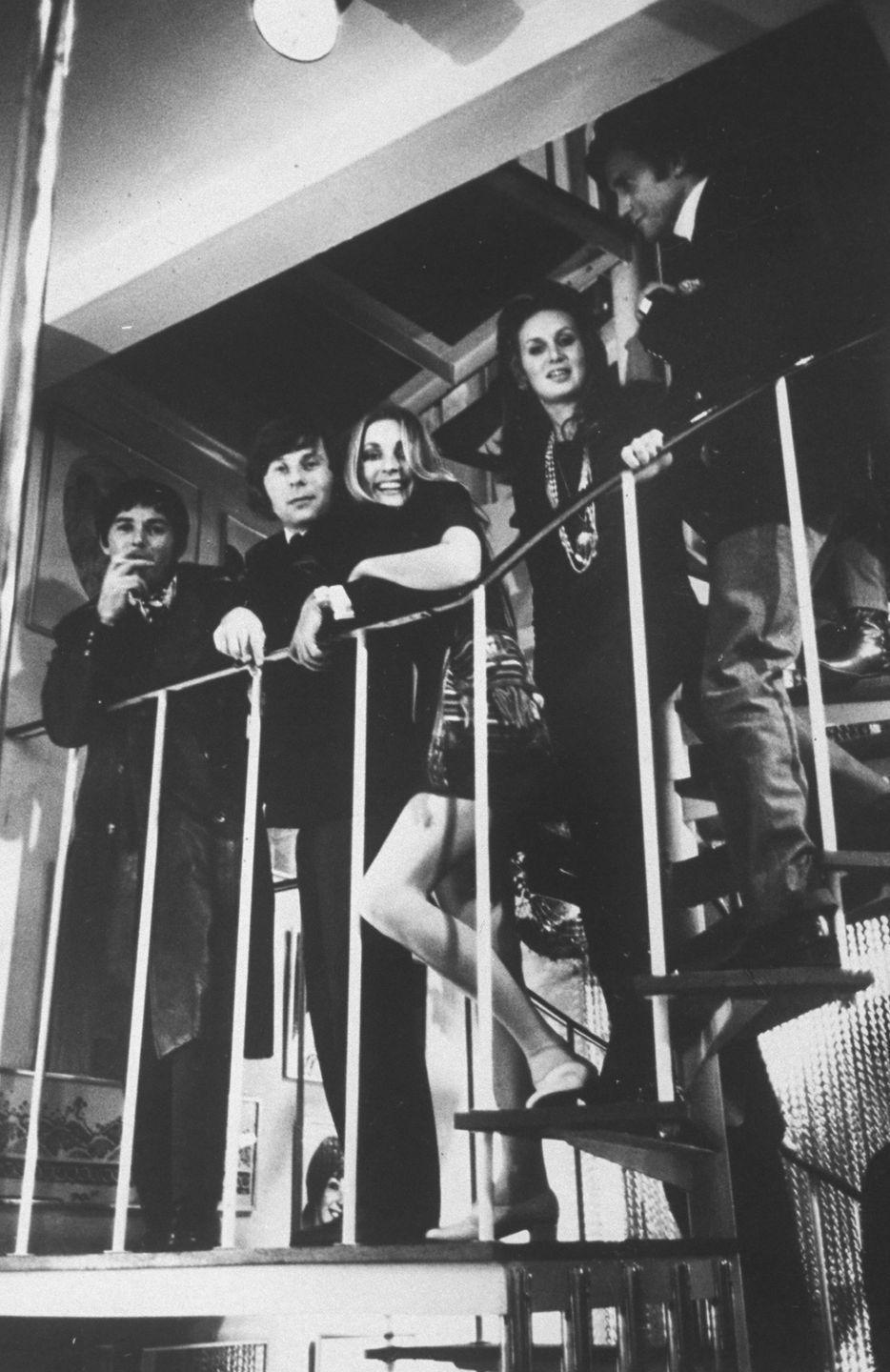 <p>Tate loved to host friends and parties. The actress (center) and her husband, Polanski, pose on the spiral staircase in their London apartment with friends, which included Jay Sebring (left). </p>