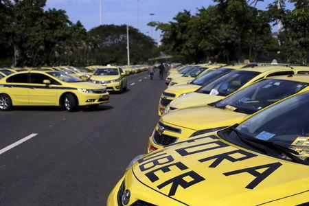 """Taxis parked on the street, one with words which reads """"Out Uber"""", are pictured during a protest against the online car-sharing service Uber in Rio de Janeiro, Brazil July 24, 2015. REUTERS/Ricardo Moraes"""