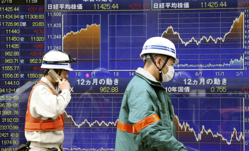 <p> Workers walk by an electronic stock board of a securities firm in Tokyo, Monday, Feb. 18, 2013. Japan's benchmark stock index jumped Monday after Group of 20 finance officials avoided directly criticizing Prime Minister Shinzo Abe's new government for trying to force down the yen. Other Asian stock markets were mixed. (AP Photo/Koji Sasahara) </p>