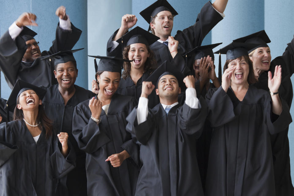College graduates cheering in caps and gowns