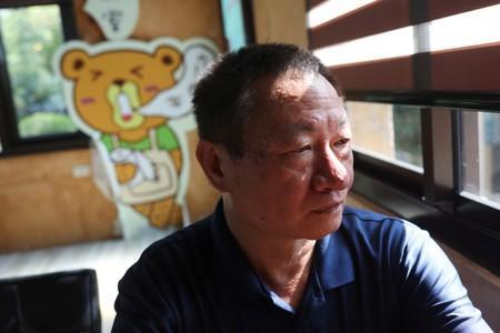 Lin Guo-cing, a senior official of the Chinese Unity Promotion Party, sits at a cafe at a theme park he is planning to introduce to the China market, in Chiayi