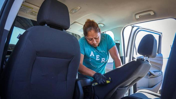 Angelica Rodriquez helps detail and clean a used vehicle being readied for sale at Flagship Motors in Nampa.