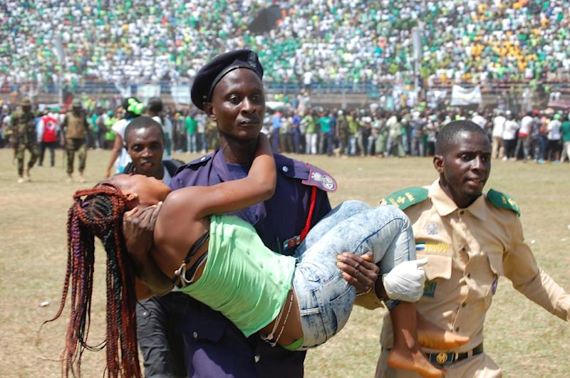 A woman injured during the stampede is carried away by a policeman