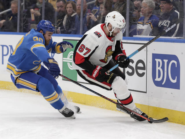 St. Louis Blues' Ryan O'Reilly (90) tips the puck away from Ottawa Senators' Ben Harpur (67) during the second period of an NHL hockey game Saturday, Jan. 19, 2019, in St. Louis. (AP Photo/Tom Gannam)