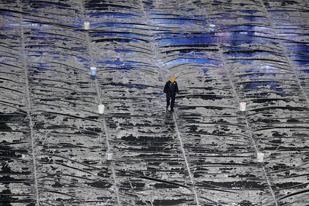 A groundskeeper walks in the rain across a tarp covering the field before an AFC divisional NFL playoff football game between the New England Patriots and Indianapolis Colts in Foxborough, Mass., Saturday, Jan. 11, 2014. (AP Photo/Matt Slocum)