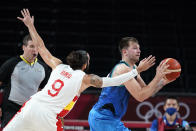 Slovenia's Luka Doncic passes ahead of Spain's Ricky Rubio (9) during a men's basketball preliminary round game at the 2020 Summer Olympics, Sunday, Aug. 1, 2021, in Saitama, Japan. (AP Photo/Charlie Neibergall)
