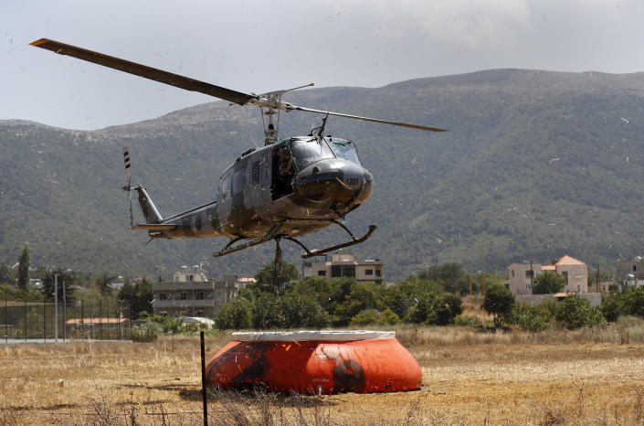 A Lebanese army helicopter flies over a water storage container as it refills a tank to extinguish a forest fire, at Qobayat village, in the northern Akkar province, Lebanon, Thursday, July 29, 2021. Lebanese firefighters are struggling for the second day to contain wildfires in the country's north that have spread across the border into Syria, civil defense officials in both countries said Thursday. (AP Photo/Hussein Malla)