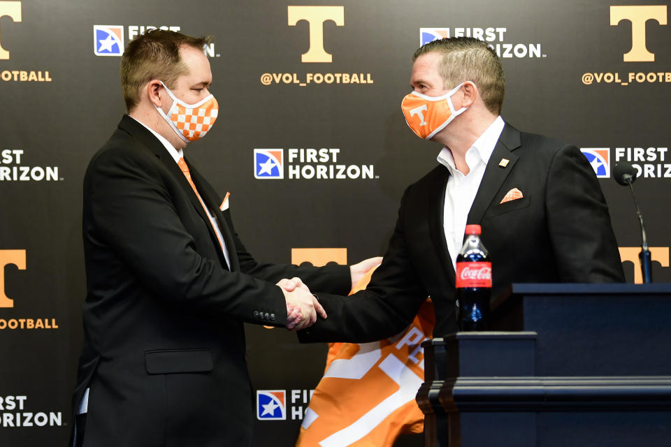 New Tennessee coach Josh Heupel, left, shakes hands with athletic director Danny White after being presented a jersey during an introductory news conference on Jan. 27. (AP)