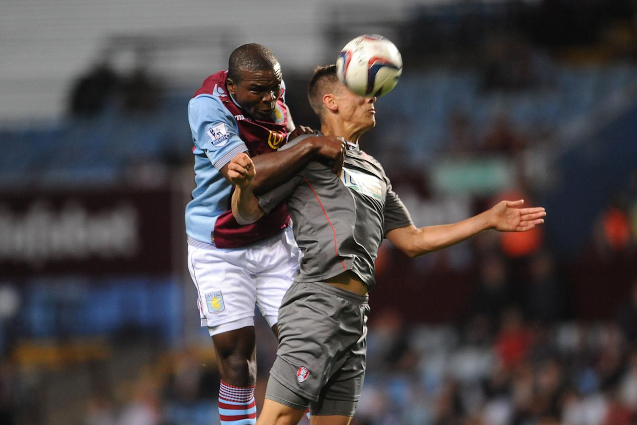 Aston Villa's Jores Okore and Rotherham United's Alex Revell challenge for the ball in the air during the Capital One Cup, Second Round match at Villa Park, Birmingham.