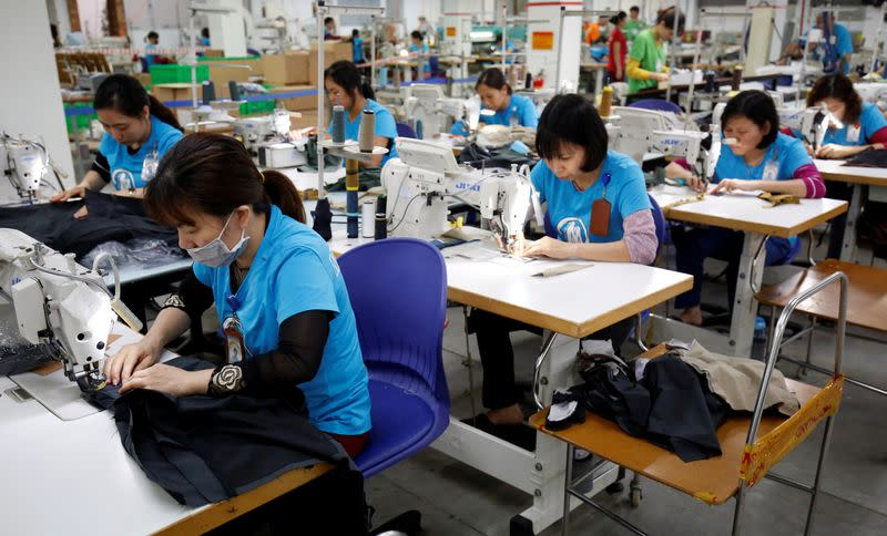 FILE PHOTO: Labourers work at export garment Maxport factory in Hanoi