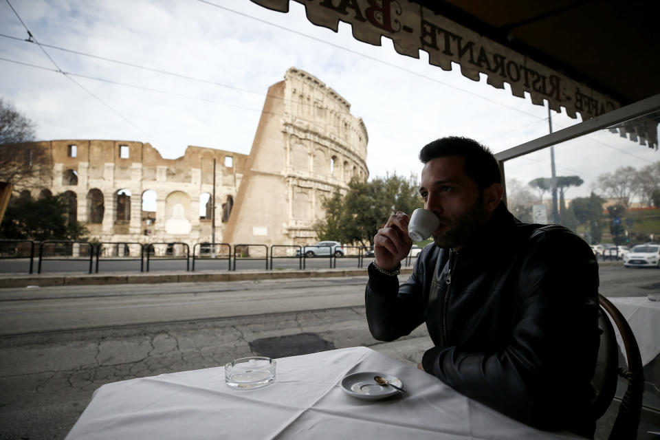 A man sips coffee in front of Rome's ancient Colosseum after its reopening Monday, Feb. 1, 2021, in a partial lifting of restriction measures aimed at containing the spread of COVID-19. Italy has eased its coronavirus restrictions Monday for most of the country downgrading Lazio and other regions from medium-risk orange zones to lower-risk yellow zones. (Cecilia Fabiano /LaPresse via AP)