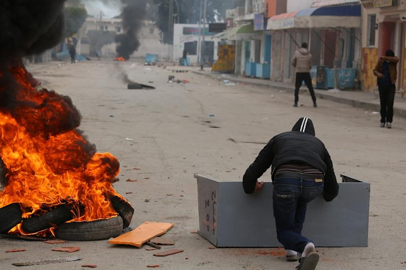 Tunisian youths throw stones towards a police station on January 11, 2017, in the Tunisian southern border town of Ben Guerdane, as locals protest the closing of a border crossing with Libya vital to the region's economy
