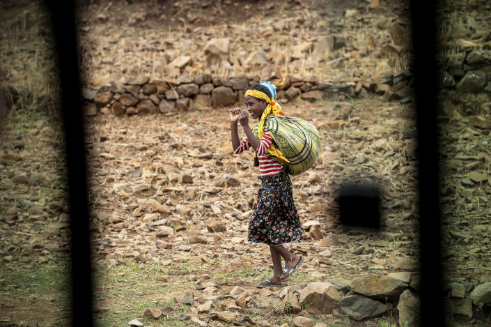 A girl walks by the side of the road, seen through a partially-open window of a vehicle, between Gondar and Danshe, a town in an area of western Tigray annexed by the Amhara region during the ongoing conflict, in Ethiopia Saturday, May 1, 2021. Ethiopia faces a growing crisis of ethnic nationalism that some fear could tear Africa's second most populous country apart, six months after the government launched a military operation in the Tigray region to capture its fugitive leaders. (AP Photo/Ben Curtis)