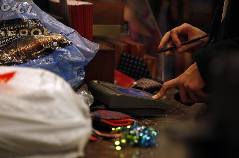 A customer signs the credit card pad as he pays for a purchase at Macy's on Black Friday in New York