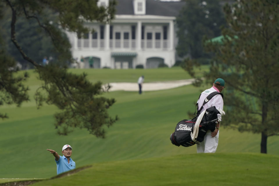 Sung Kang, of South Korea, talks to his caddie on the seventh fairway during a practice round for the Masters golf tournament Wednesday, Nov. 11, 2020, in Augusta, Ga. (AP Photo/Charlie Riedel)