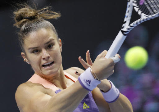 Maria Sakkari of Greece returns the ball to Belinda Bencic of Switzerland during the St. Petersburg Ladies Trophy-2020 tennis tournament match in St.Petersburg, Russia, Friday, Feb. 14, 2020. (AP Photo/Dmitri Lovetsky)