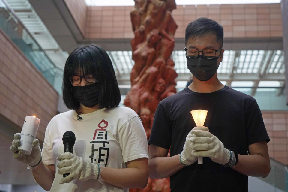 """In this Sunday, May 2, 2021, photo, Hong Kong Alliance in Support of Patriotic Democratic Movements of China Vice Chairperson Chow Hang-tung, left, stands in front of the """"Pillar of Shame"""" statue, a memorial for those killed in the 1989 Tiananmen crackdown, at the University of Hong Kong. High-profile Hong Kong activist Joshua Wong will face an additional 10 months in jail for participating in an unauthorized Tiananmen vigil held last year to commemorate the 1989 crackdown on protesters in Beijing, as Hong Kong authorities continue tightening control over dissent in the city. (AP Photo/Kin Cheung)"""