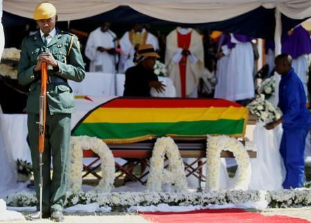 Soldier stands over the coffin of former Zimbabwean President Robert Mugabe during a church service at his rural village in Kutama, Zimbabwe