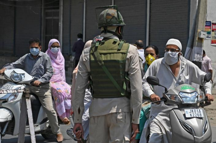 """<span class=""""caption"""">Kashmiri commuters at an Indian military checkpoint in the city of Srinagar, July 17, 2020. </span> <span class=""""attribution""""><a class=""""link rapid-noclick-resp"""" href=""""https://www.gettyimages.com/detail/news-photo/an-indian-paramilitary-trooper-speaks-with-commuters-after-news-photo/1227662789?adppopup=true"""" rel=""""nofollow noopener"""" target=""""_blank"""" data-ylk=""""slk:Tauseef Mustafa/AFP via Getty Images"""">Tauseef Mustafa/AFP via Getty Images</a></span>"""