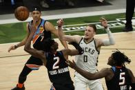 Milwaukee Bucks' Donte DiVincenzo and Oklahoma City Thunder's Shai Gilgeous-Alexander go after a rebound during the second half of an NBA basketball game Friday, Feb. 19, 2021, in Milwaukee. (AP Photo/Morry Gash)
