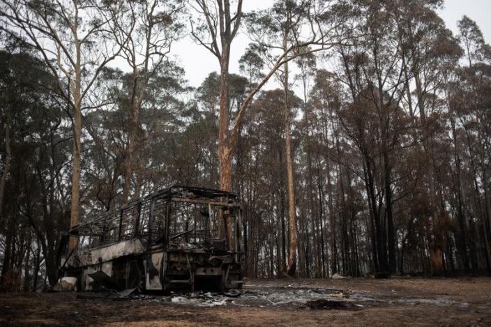 A destroyed bus is seen next to burnt bushland in the village of Mogo