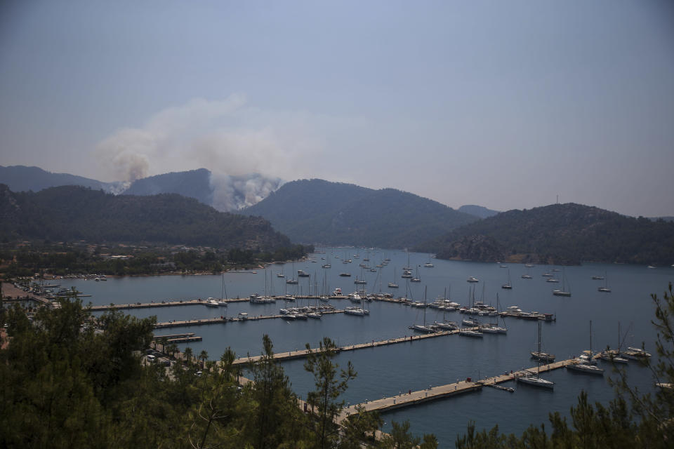 A wildfire burns the forest in Turgut village, near tourist resort of Marmaris, Mugla, Turkey, Wednesday, Aug. 4, 2021. As Turkish fire crews pressed ahead Tuesday with their weeklong battle against blazes tearing through forests and villages on the country's southern coast, President Recep Tayyip Erdogan's government faced increased criticism over its apparent poor response and inadequate preparedness for large-scale wildfires.(AP Photo/Emre Tazegul)