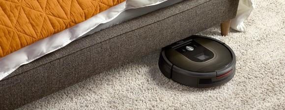 A Roomba robotic vac traveling on a rug and starting to go underneath an unidentifiable piece of furniture, possibly a bed.