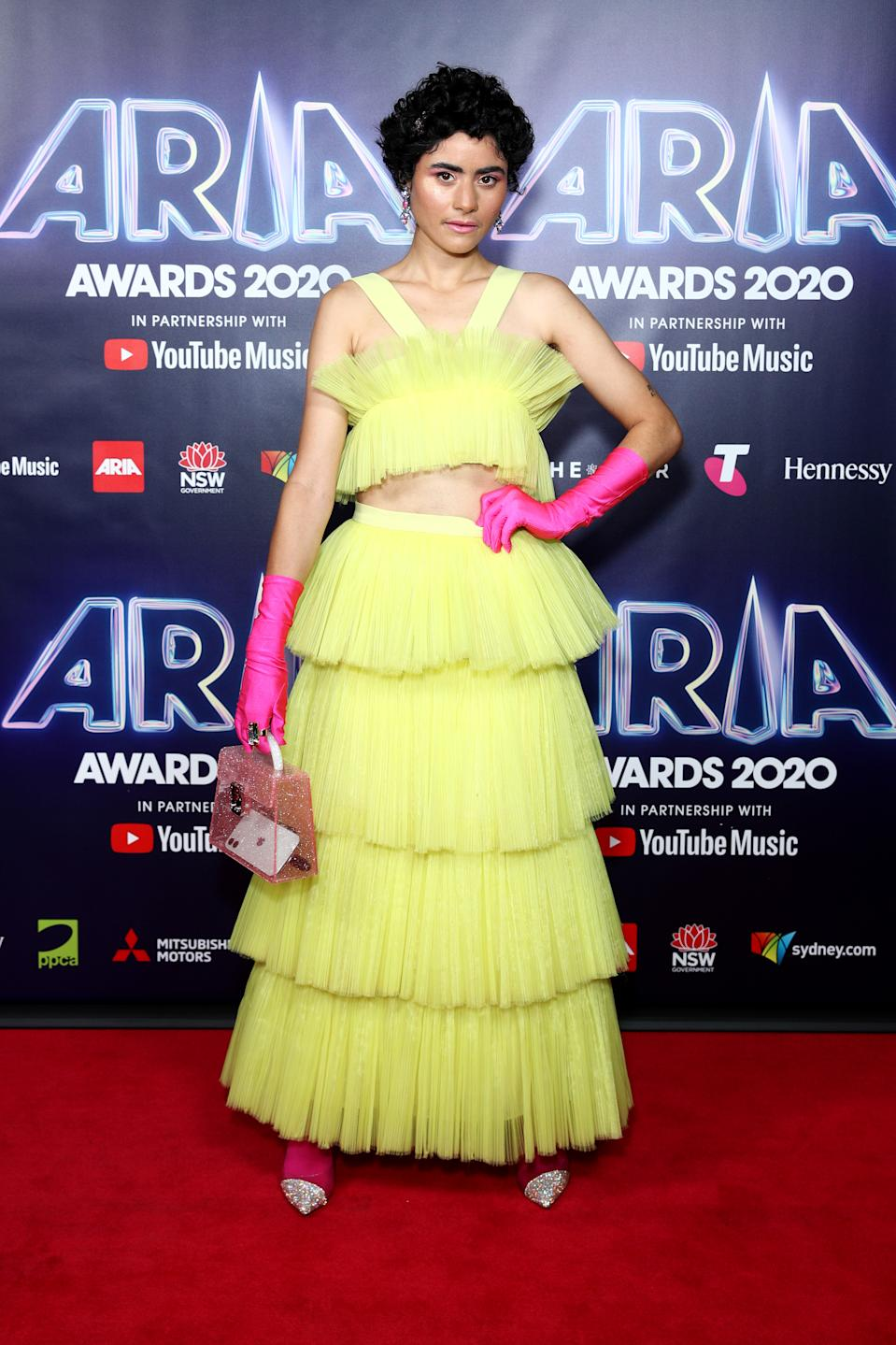 Montaigne wears a yellow tulle skirt and top with hot pink gloves and shoes on the red carpet at the 2020 ARIA Awards at The Star on November 25, 2020 in Sydney, Australia.